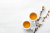 Two cups of tea and branches of blossoming apricot on a white rustic table with empty space for text or image. Top view.