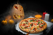 meat pizza in Halloween decoration: Scary pumpkins with painted faces, Lights of burning candles In horror smoke