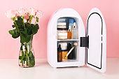 Mini fridge on pink background. Minimal composition.