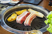 Korean grill pork belly BBQ (Samgyeopsal Gui) - trendy Korean barbecue dish, served with fresh vegetable and dipping sauce.