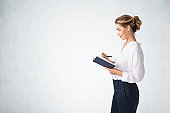 Businesswoman with notebook, side view