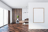 White living room with brown sofa and poster