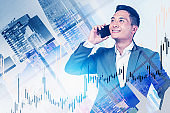 Smiling Asian trader in city, financial graph