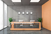Gray and orange office with clocks and reception