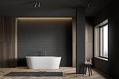 Gray tile and wood bathroom with tub and column