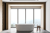 White and wooden bathroom interior with tub