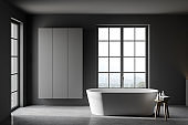 Grey bathroom with tub and cabinet
