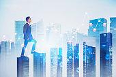 Asian man climbing bar chart in city