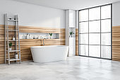 White and wood bathroom corner with tub and shelf