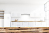 Table in blurry white kitchen with fridge