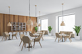 Cafe interior, many brown chairs and tables, wooden wall with lamps, dining room