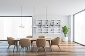 White wooden hall with brown chairs, wooden table, bookshelf and windows