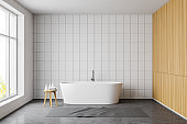 White tile and wooden bathroom interior with tub