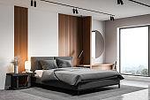White bedroom corner with round mirror