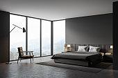 Grey master bedroom corner with armchair