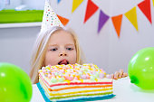 blonde caucasian girl peeking out from behind birthday cake with a funny face on birthday party. Festive colorful background with balloons