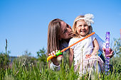 Happy mother and little daughter blow bubbles playing having fun outdoor in park at summer. Family lifestyle. Mom resting together on the green grass