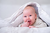Adorable smiling baby boy under white blanket in bedroom. Newborn child relaxing in bed. Family morning at home. New born infant kids