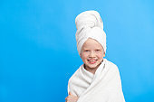 Portrait of cute little caucasian girl wrapped in white towel with bath towel on head over blue studio background. Spa procedure, bath textile