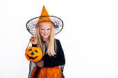 Smiling little blonde girl in witch costume with candy bucket pumpkin Halloween on white studio background. copyspace