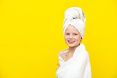 Portrait of cute little caucasian girl wrapped in white towel with bath towel on head over yellow studio background. Spa procedure, bath textile