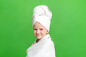 Portrait of cute little caucasian girl wrapped in white towel with bath towel on head over greenstudio background. Spa procedure, bath textile