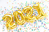 Happy New year 2021 celebration. Gold foil balloons numeral 2021 and confetti on white background. Flat lay