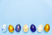 Happy Easter. Frame for text made of easter eggs trendy colored classic blue, white and golden on blue. Minimal style, top view, flatlay, copy space