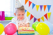 Blonde caucasian boy sits thoughtfully and dreamily at festive table near birthday rainbow cake and makes a wish. Colorful background with balloons