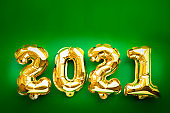 Happy New year 2021 celebration. Gold foil balloons numeral 2021 and festive bokeh lights on green background. Flat lay