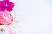 Spa cosmetic and beauty treatment concept. Pink spa sea salt and purple orchid on white wooden background. copyspase flatlay