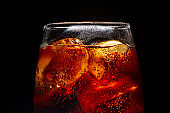 Soft drink glass with ice splash on dark background. Cola glass in celebration party concept.
