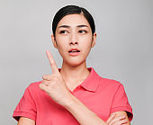 young beautiful asian woman wore pink t shirt, Showed idea expression , on gray background
