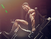 bodybuilder fitness man pumping up legs muscles