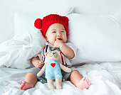 Portrait of a newborn Asian cute baby boy wore blue Infant bodysuit crawling on the bed , Charming Fat baby 5 month old enjoy and happy,soft selective focus