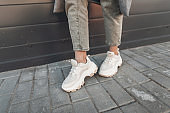 Close-up female legs in fashion jeans in stylish leather sneakers near building in city. Fashionable woman in casual wear on walk. Trendy seasonal collection of youth sneakers. Spring women's shoe.