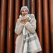 Fashion model of a pretty happy young woman with a cute smile in fashionable faux fur coat in a knitted stylish hat with a woolen plaid scarf posing near a metallic wall in the city. Cheerful girl.