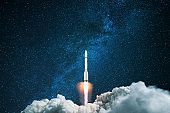 Rocket starts in the night starry sky. A spaceship flies into outer space. Concept of travel to other planets