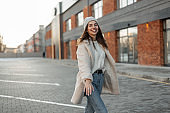 Glamorous funny young woman with smile in a knitted hat in a stylish sweater in a fashionable faux fur coat in jeans walks on a parking near a brick building. Joyful girl model outdoors in the city.