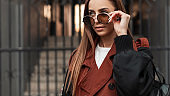 Fresh portrait urban girl in trendy clothes outdoors. Modern young hipster woman in stylish trench coat with black leather backpack puts on fashionable sunglasses near vintage iron gate in street.