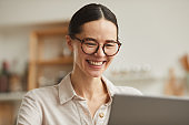 Smiling Businesswoman Using Laptop at Home