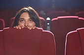 Scared Woman Hiding in Cinema