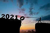 new year concept, silhouette of man pull number down to success in 2021