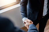 successful contract negotiate and handshake concept, two businessman shake hand with partner to celebration partnership, teamwork, business deal in room meeting after success communication, agreement