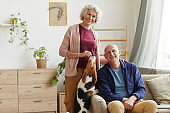 Smiling Senior Couple with Dog at Home