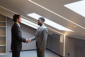 Business Partners Shaking Hands in Empty Office