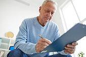 Senior Man Filling Patients Report