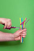 Cutting plastic straws. Metal drinking straw. Reduce plastic waste