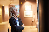 Mature Woman Looking at Paintings in Art Gallery