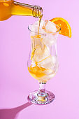Pouring orange syrup in a glass with ice cubes. Making lemonade